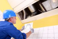 mechanic checking blue print on an air conditioning system
